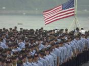 English: Yokosuka, Japan (Sep. 11, 2002) -- The crew of USS Kitty Hawk (CV 63) stands at attention as the ensign is raised during morning colors. A special memorial service is being held in remembrance of those lost from the events of September 11, 2001.
