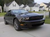 English: A picture of a black 2011 Ford Mustang v6 Coupe with the optional Performance package.