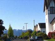 Street and houses in the Dickens neighbourhood of East Vancouver (with North Shore Mountains in background)