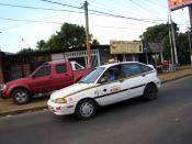 A taxicab in Managua with a missing hubcap on the lower wheel.