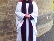 An Anglican priest wearing a cassock, academic hood, English-style surplice, and tippet as his choir dress.