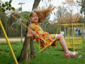 A girl on a garden swing. Original caption: : Bincadeira de criança : eu também me acabei nesse balanço...