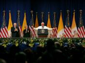English: Caption: Pope Benedict XVI, joined on stage by Vice President Dick Cheney and Mrs. Lynne Cheney, gestures to the faithful Sunday, April 20, 2008 at a farewell ceremony for the Pope at John F. Kennedy International Airport in New York.