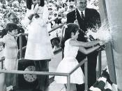 Caroline Kennedy breaks a bottle of champagne against the hull of the US Navy aircraft carrier named after her father. Jackie and John, Jr. look on with smiles at the launch ceremonies for the USS John F. Kennedy (CV-67) in May 1967.