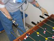 A soldier in the U.S. Army plays fooz-ball with two prosthetic limbs. Courtesy of the U.S. Army, by Walter Reed photographers. Photo Courtesy of U.S. Army