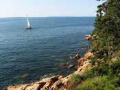 English: a beach in maine on a clear day with a sailboat