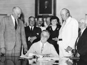 Roosevelt Signs The : President Roosevelt signs Social Security Act, at approximately 3:30 pm EST on 14 August 1935. Standing with Roosevelt are Rep. (D-NC); unknown person in shadow; Sen. Robert Wagner (D-NY); Rep. John Dingell (D-MI); unknown man in bow