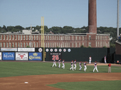 English: Members of the Lowell Spinners warm up in right field at LeLacheur Park, June 2009, with historic mill in background.