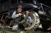 English: World War II Infantryman, kneeling in front of M3 Half-track, holds and sights an M1 Garand rifle. Fort Knox, Kentucky, June 1942. Français : Un fantassin américain de la Seconde Guerre Mondiale, agenouillé près d'un Halftrack M3, tenant en joue