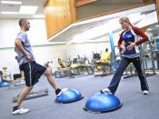 Personal trainer showing a client how to exercise the right way and educating them along the way. The semi-spherical device is a BOSU. Category:Fitness Category:Fitness_training Category:Personal_training Category:Stretching Category:Challenges to physica