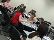 English: Shows students in a university classroom tutorial at tables, working on a problem-solving exercise as part of Motivation and emotion.