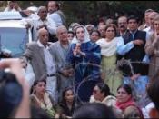 Former Prime Minister of Pakistan, Benazir Bhutto (center), speaks to supporters outside her house.