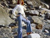 Tall natural redhead Erika on a North Devon beach in the UK, wearing bell bottom jeans.