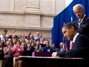English: United States President Barack Obama signs into law the American Recovery and Reinvestment Act of 2009 as Vice President Joe Biden looks on.