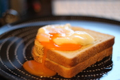 English: A single broken poached egg on 2 pieces of toast bread.