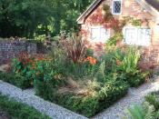 English: Part of a parterre in an English garden. Photo taken in September 2007, showing the development of the garden. The beds are edged with Ilex crenata (Box-leaved holly) and are planted with orange and red-flowered perennials to echo the colour of t