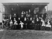 English: Extended family outside the Jenkinson home, Woodford, Queensland, ca. 1906 Multi-generational family? photograph taken in front of a wooden house with front verandah. Child on the left is wearing a sailor suit and riding a rocking horse. Oldest m