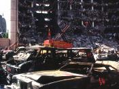 The bombed remains of automobiles with the bombed Federal Building in the background. The military is providing around the clock support since a car bomb exploded inside the building on Wednesday, April 19, 1995.
