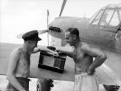 English: Black and white photograph of Ron McCann (former Collingwood player) and Frank Curcio (active Fitzroy player) listening to the 1944 VFL Grand Final on the wing of a Kittyhawk. Photograph taken at Noemfoor Island, Dutch New Guinea in September 194
