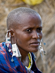 English: Maasai woman in traditional clothing and jewellery in the Serengeti National Park, Tanzania. Français : Femme Maasaï portant un costume et de la bijouterie traditionnels. Photo prise dans le Parc national du Serengeti, en Tanzanie.