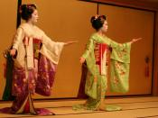 Two maiko performing in Gion. *The lady on the left likely has more experience than the lady on the right; this is evidenced by her white collar (in contrast to the red collar on the right, indicating her maiko/apprentice geisha status).*