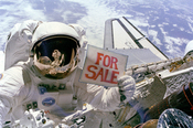 A NASA astronaut jokingly advertises a recovered defective satellite for sale during a space walk