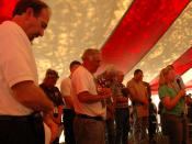 English: Greensburg, KS, May 11, 2007 --- Greensburg Mayor Lonnie McCollum (center, hat in hand) prays with the people of his community at the first Greensburg Town Hall Meeting on Friday. The tent was erected so people have a place to meet. FEMA Photo by