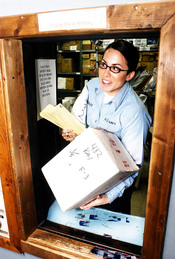 English: Naval Station Sigonella, Italy (Jan. 7, 2003) -- Postal Clerk Seaman Olivia Robles from Modesto, Calif., hands packages to a postal customer through the base post office package pick-up window. Seaman Robles was called to duty from inactive ready