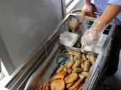 A Vietnam Railways employee offers a variety of foods from a cart on a train from Hanoi to Danang.