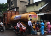 A truck distributing water to residents the seem not to have a (working) water supply line in their houses. Seems like a local politian sponsored the water as part of his election campaign. The timing is a bit odd since Indian monsoon takes place ongoing
