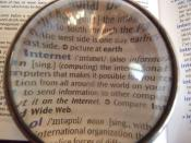 A picture of a dictionary viewed with a lens on top of it, at the word