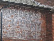 English: Faded advert, Welland Road, Hanley Swan I can make out the words, Ironmongery, Drapery and Stores but this appears to be two different adverts and the top word is indistinct. Current use of the building is a bakery.