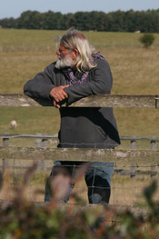 Arthur Uther Pendragon standing outside of the Stonehenge monument fence