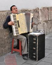 English: Accordion player in a street in the historic centre of Quito, Ecuador. Español: Hombre tocando el acordeón en una calle del Centro Histórico de Quito, Ecuador. Français : Joueur d'accordéon dans une rue du Centre historique de Quito, Équateur.