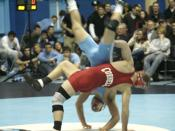 Two college students wrestling (collegiate, scholastic, or folkstyle) in the United States.