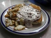 A serving of biscuits and gravy, accompanied by home fries