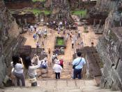 Tourists taking pictures at the khmer Pre Rup temple ruins, an example of cultural tourism.
