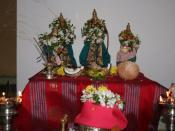 English: Celebrating Sri Rama navami in 2007. Rama, Sita and Lakshmana idols on a table. Offerings of coconut and flowers in front. Burning oil lamps on either side.