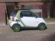Smart Car: White and green electric car charging - Aston Street
