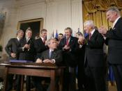 English: President George W. Bush acknowledges the applause of legislators and administration officials Tuesday, August 2. 2005 in the East room of the White House, as he signs the CAFTA Implementation Act.