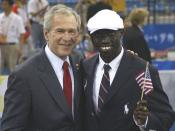 President George W. Bush poses for a photo with U.S. Olympic runner Lopez Lomong Friday, Aug. 8, 2008, in Beijing prior to Opening Ceremonies of the 2008 Summer Olympic Games. Lopez Lomong, a survivor of the violence in his native Sudan, now a U.S. citize