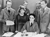 English: D.W. Griffith, Mary Pickford, Charlie Chaplin (seated) and Douglas Fairbanks at the signing of the contract establishing United Artists motion picture studio in 1919. Lawyers Albert Banzhaf (left) and Dennis F. O'Brien (right) stand in the backgr