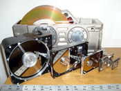 Six hard disk drives with cases opened showing platters and heads; 8, 5.25, 3.5, 2.5, 1.8 and 1 inch disk diameters are represented.