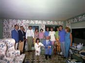 Family group portrait in sunroom with flowered drapes and upholstery with all standing behind Joseph who is seated, Jackie is kneeling next to him