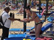 English: A woman wearing a bikini inspects a salesman's necklaces on a popular beach on a sunny day. Huatulco, Oaxaca, México
