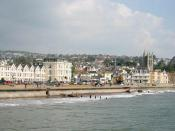 English: Teignmouth Seafront from the Pier. Teignmouth has for a long time been a small port exporting clay and granite from the docks at the mouth of the River Teign. This photograph however shows the town seafront - Teignmouth as a tourist town. The tou