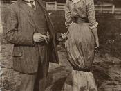 A postcard (circa 1911) depicting a man and a women dressed in the fashion of the era. Woman wears a hobble skirt, man points to her with his thumb. Caption: The Hobble Skirt