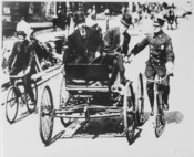 Traffic violator driving a 1900-vintage car being stopped by a policeman on a bicycle, 1949 - NARA - 513352