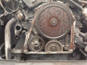 Front view of timing gears in a Ford Taunus V4 engine in a SAAB 96. The (fibre) balance shaft gear (lower left) has lost its teeth due to bearing failure. The other small (steel) gear is the crankshaft gear. The largest (fibre) gear is the camshaft gear.