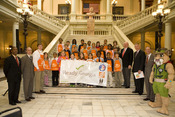 Governor Sonny Perdue, GEMA/OHS Director Charley English, GEMA/state staffers and Georgia elementary school students pose with a banner at the official launch of Ready Georgia.